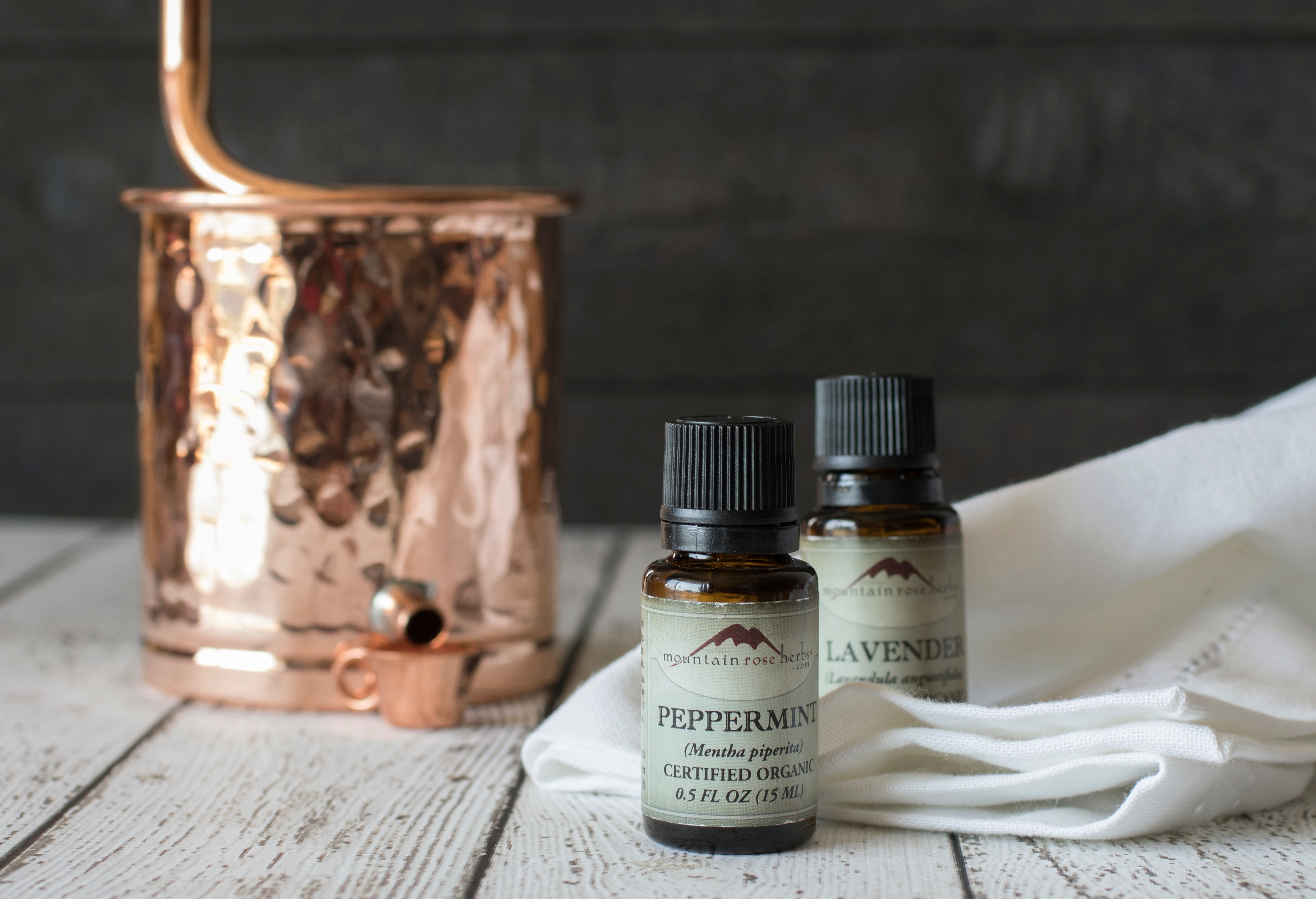 Small bottle of peppermint essential oil sitting next to a copper still on a wooden table
