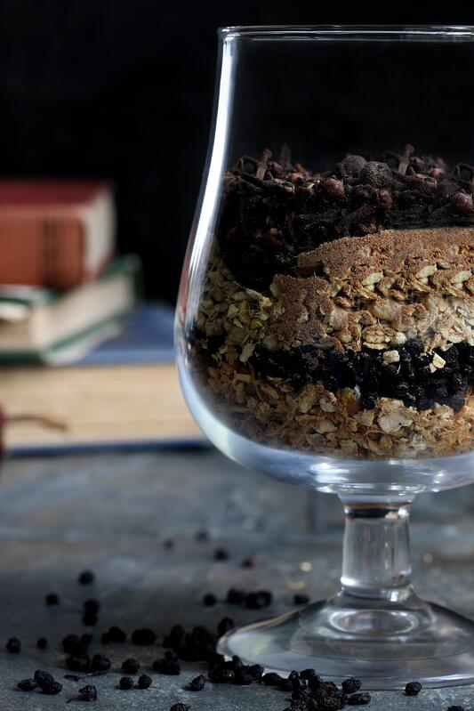 Snifter glass filled with dried berries and spices with books in background