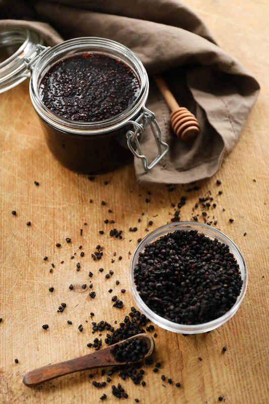 Ingredients for making elderberry vinegar are scattered on a table top. Finished vinegar rests in a large storage jar next to a wooden honey dipper and brown cloth towel, while freshly dried elderberries rest in a glass bowl next to a wooden spoon.