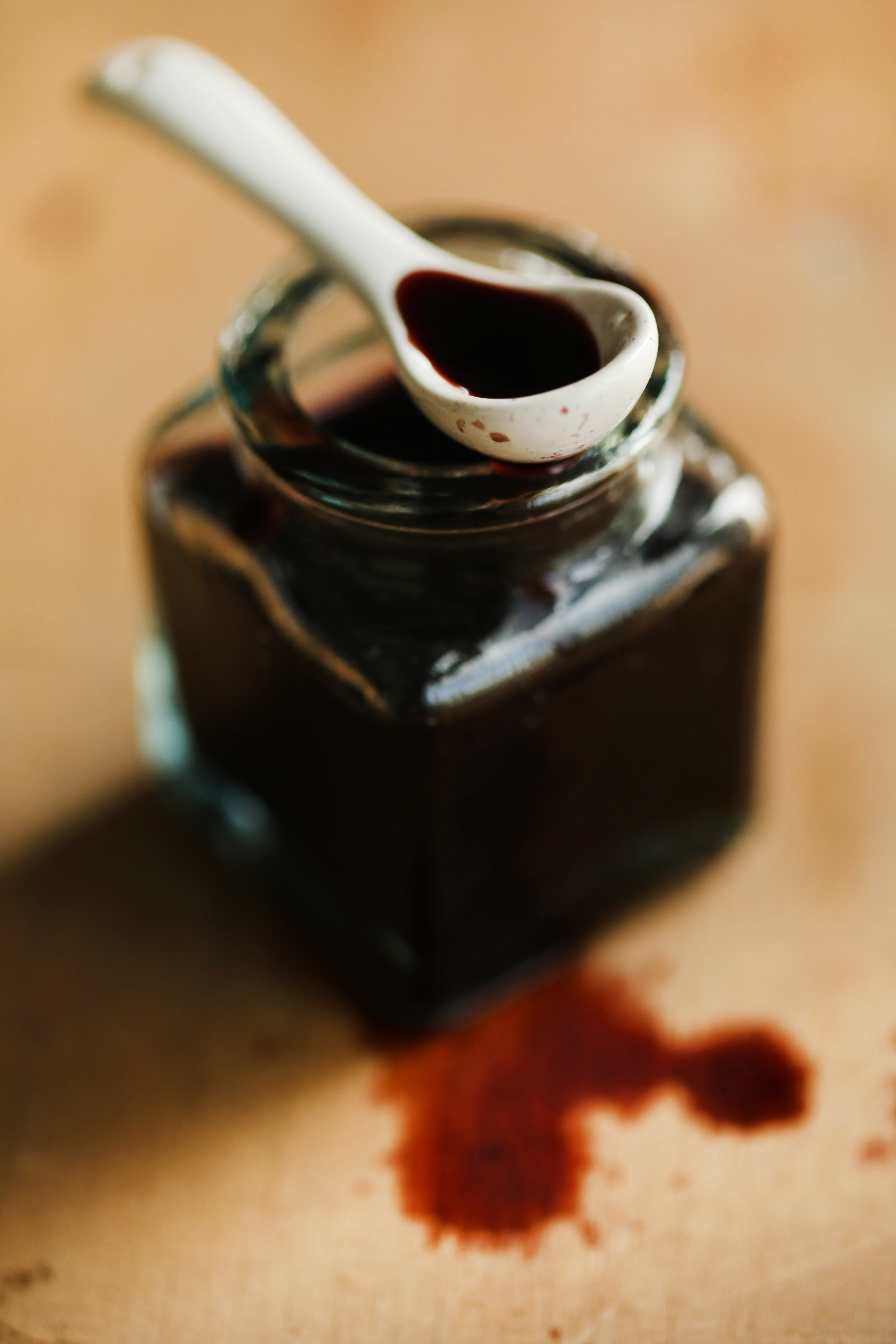 A white spoon full of dark, elderberry vinegar rests on the mouth of a clear jar full of dark, syrupy liquid. Several drops of dark red vinegar drips onto a wood surface.