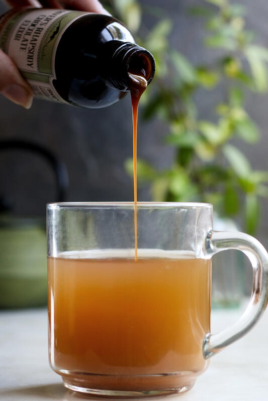 An herbal chocolate syrup is added to a warm beverage in a clear glass mug. Herbal syrups are used for natural wellness.