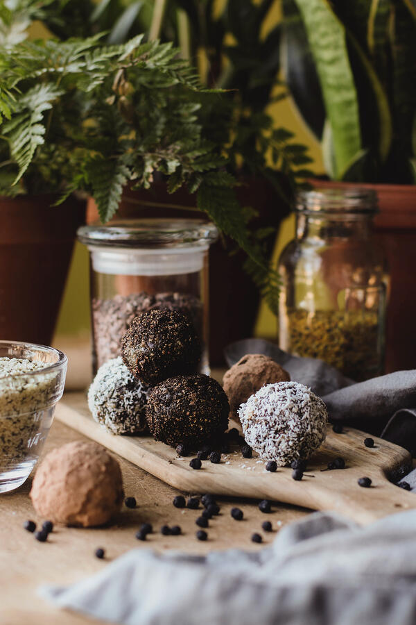 Protein Energy Balls rolled in cocoa and coconut laid out on a cutting board amidst hemp seeds, cacao and other ingredients.