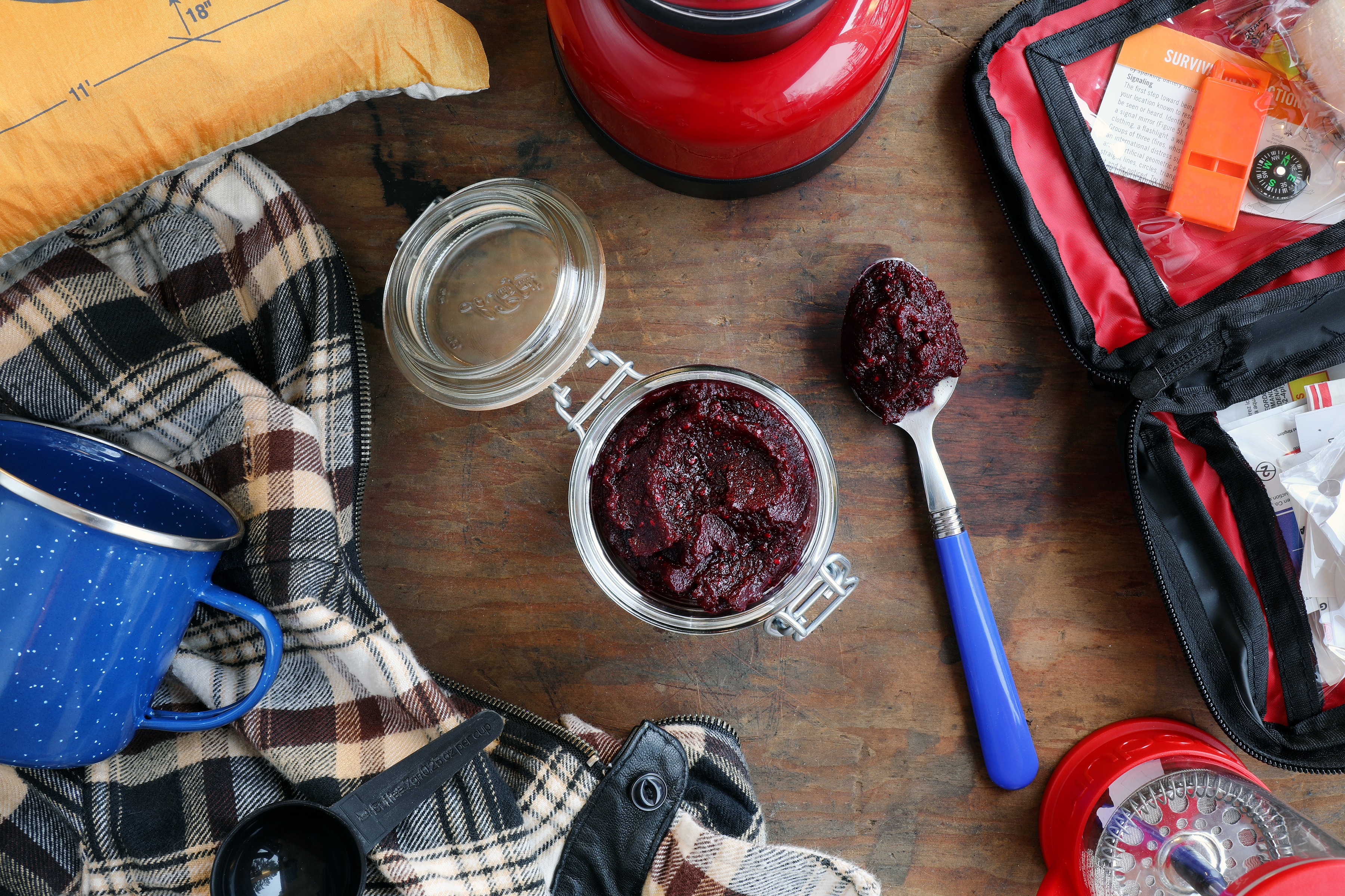 Clamp jar with deep red paste surrounded by camping gear and accessories.