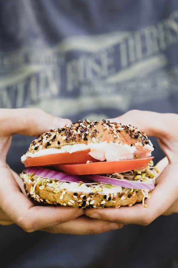 Hands holding an everything bagel sandwich.