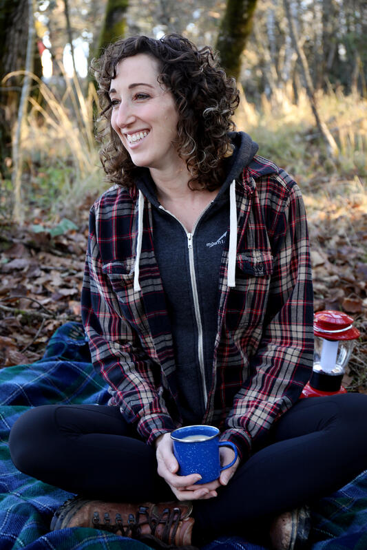 Young woman in a flannel shirt, smiling, while holding a warm beverage in a natural setting.