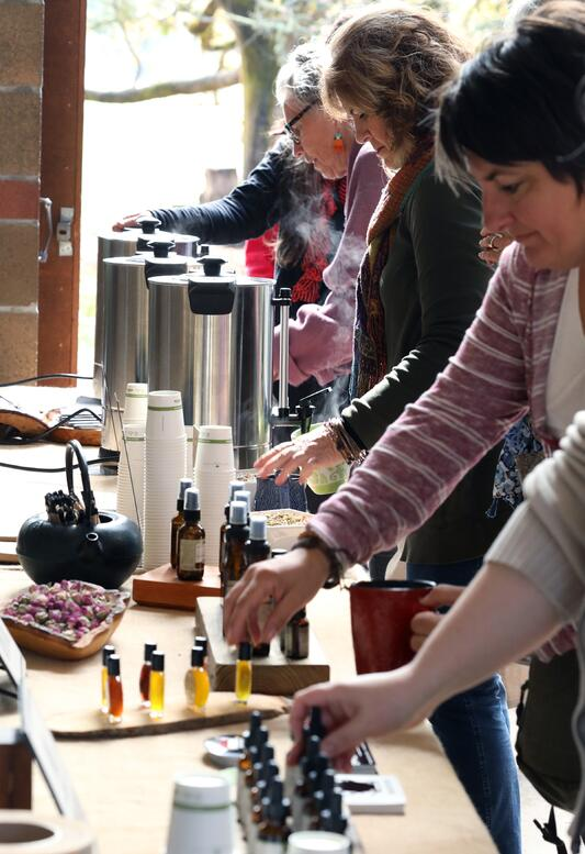 People reaching to sample tinctures, aroma sprays and tea at local event the Free Herbalism Project with Mountain Rose Herbs
