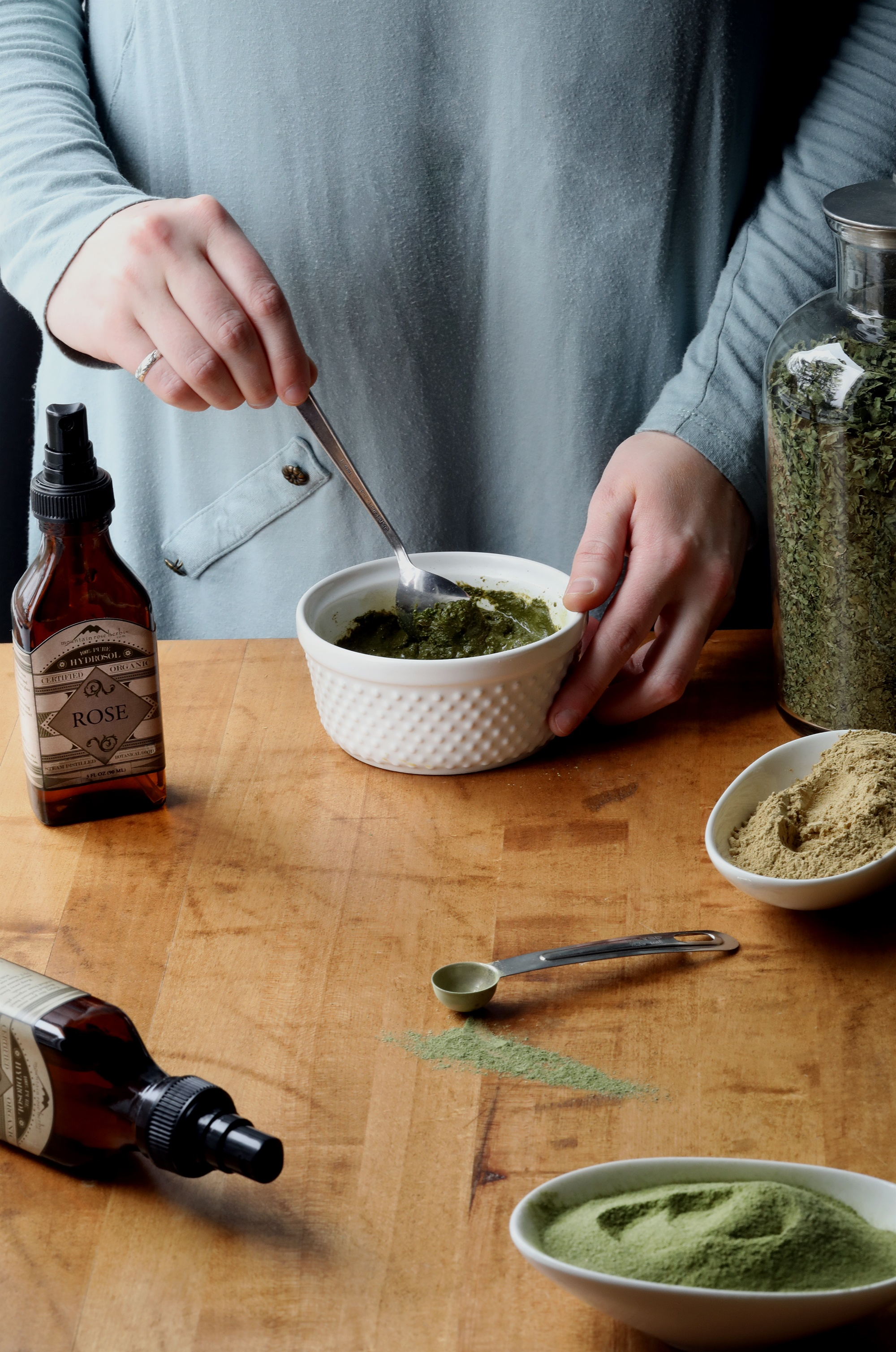 Hands mixing ayurvedic face mask from herbs and floral hydrosols