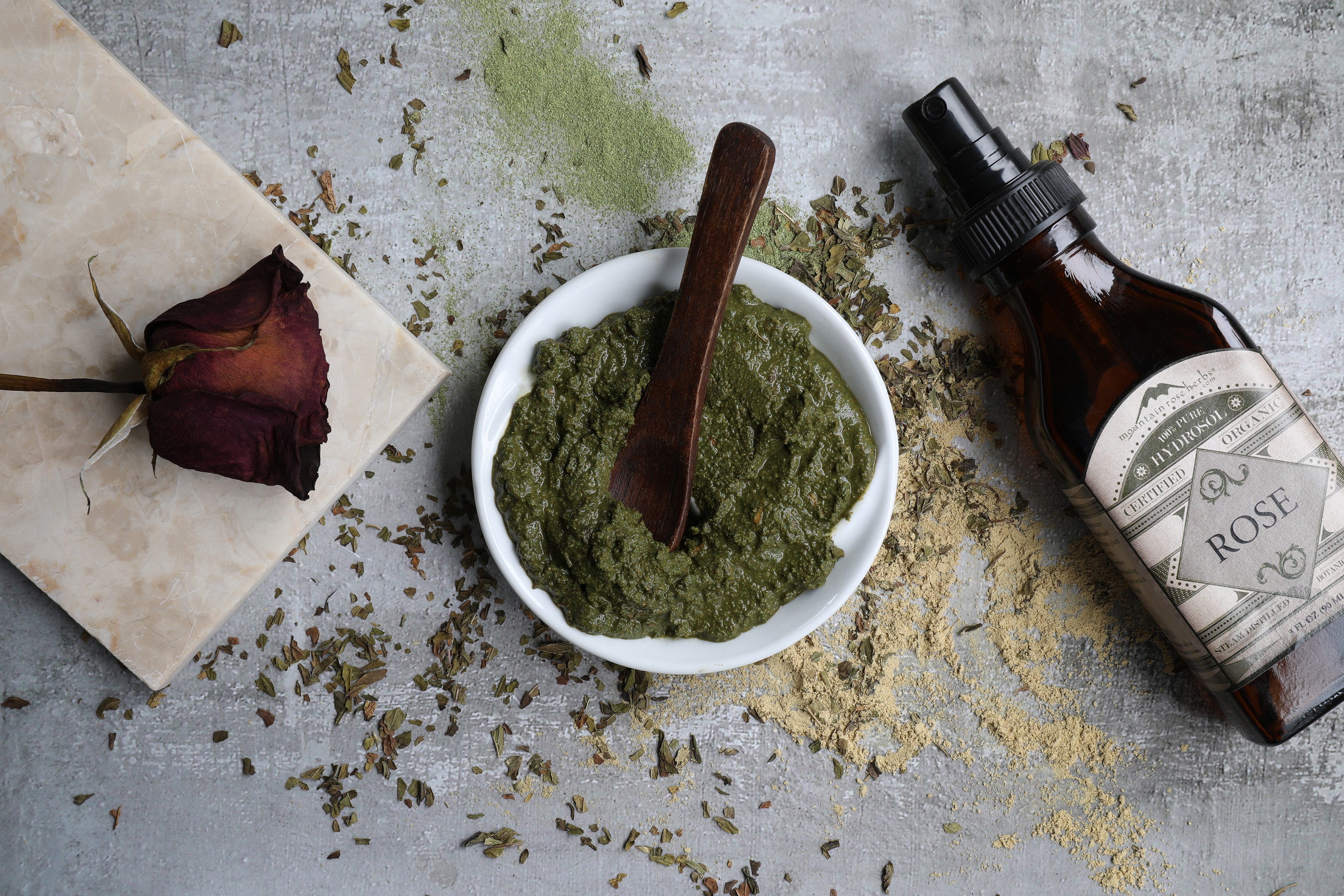 White bowl filled with green paste with displayed botanicals and a bottle of hydrosol.