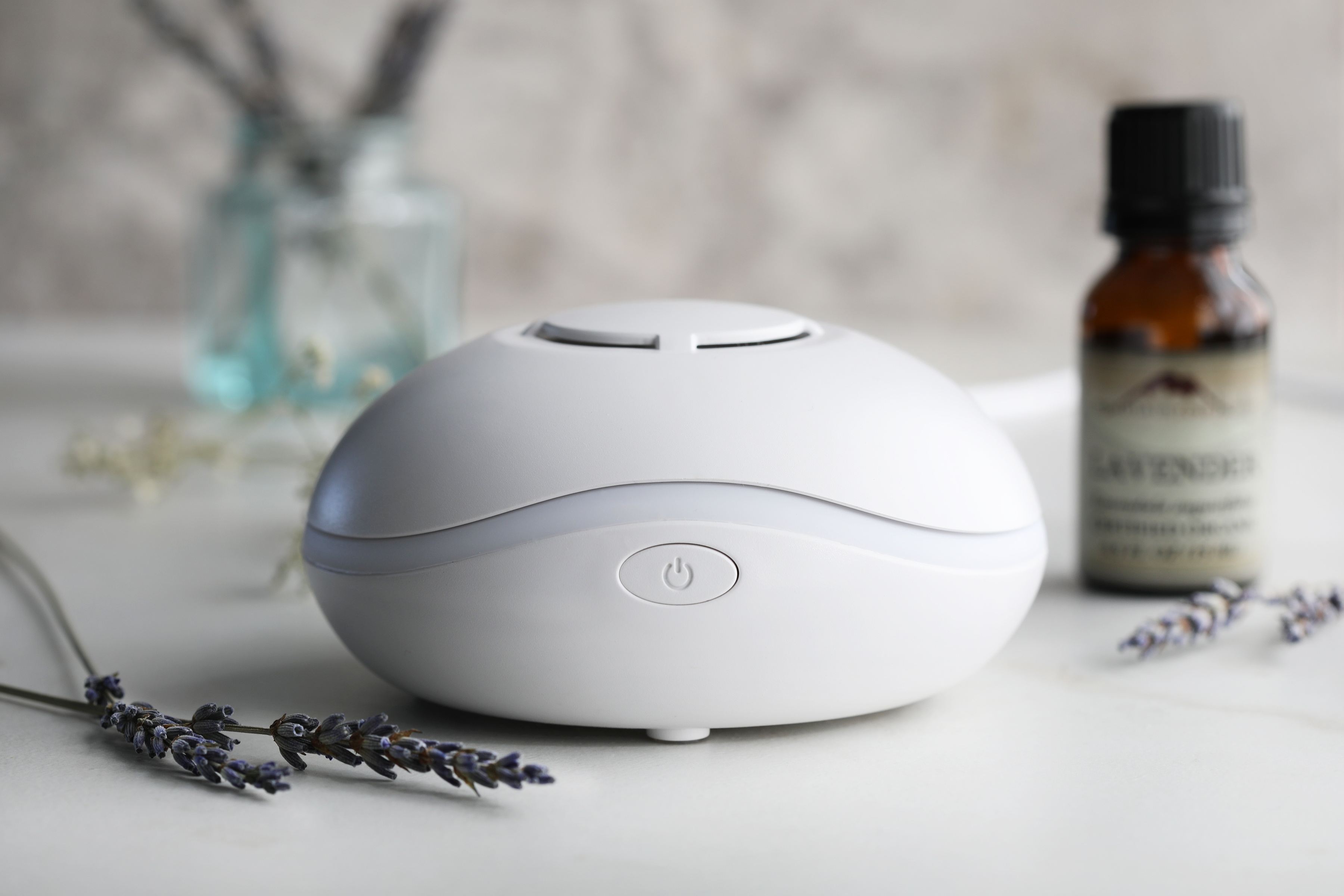 Aroma diffuser with lavender essential oil and lavender flowers sitting by diffuser