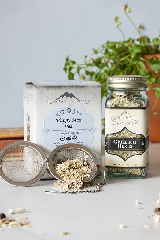 Box of happy man tea, bottle of grilling herbs, and tea infuser with loose-leaf tea