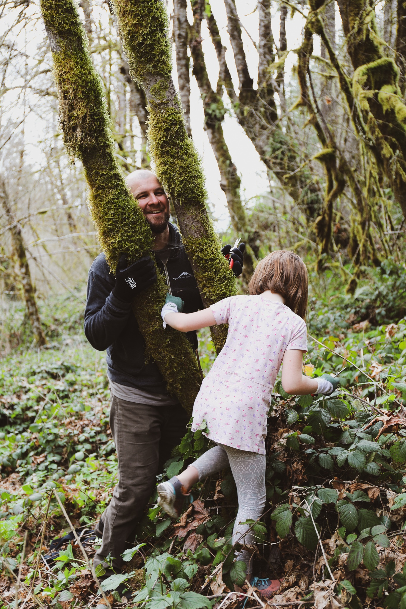 Father and daughter in forest playing and touching trees