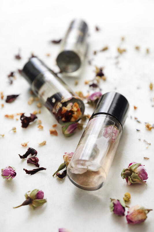Clear perfume bottles with real flowers inside surrounded by more dried flowers.