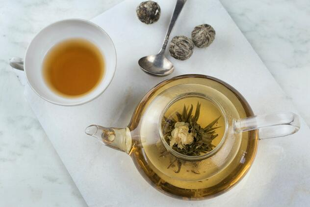 Glass teapot with brewed flowering tea, teacup with brewed green tea, cutting board