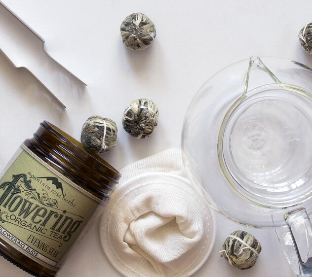 Jar of flowering tea with tea making supplies including tea pot, tea squeezer
