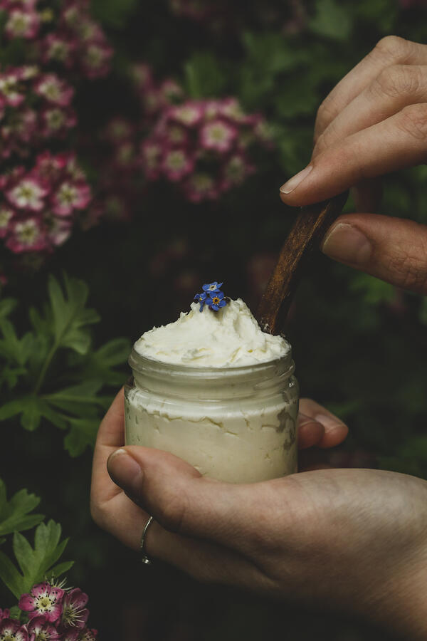 A person holding a jar of homemade nipple cream with flowers.