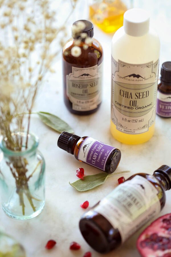 Ingredients on a table to make DIY foaming hand and body soap recipe, including rosehip seed oil, chia seed oil, pomegranate seed oil and clary sage and vetiver essential oils.