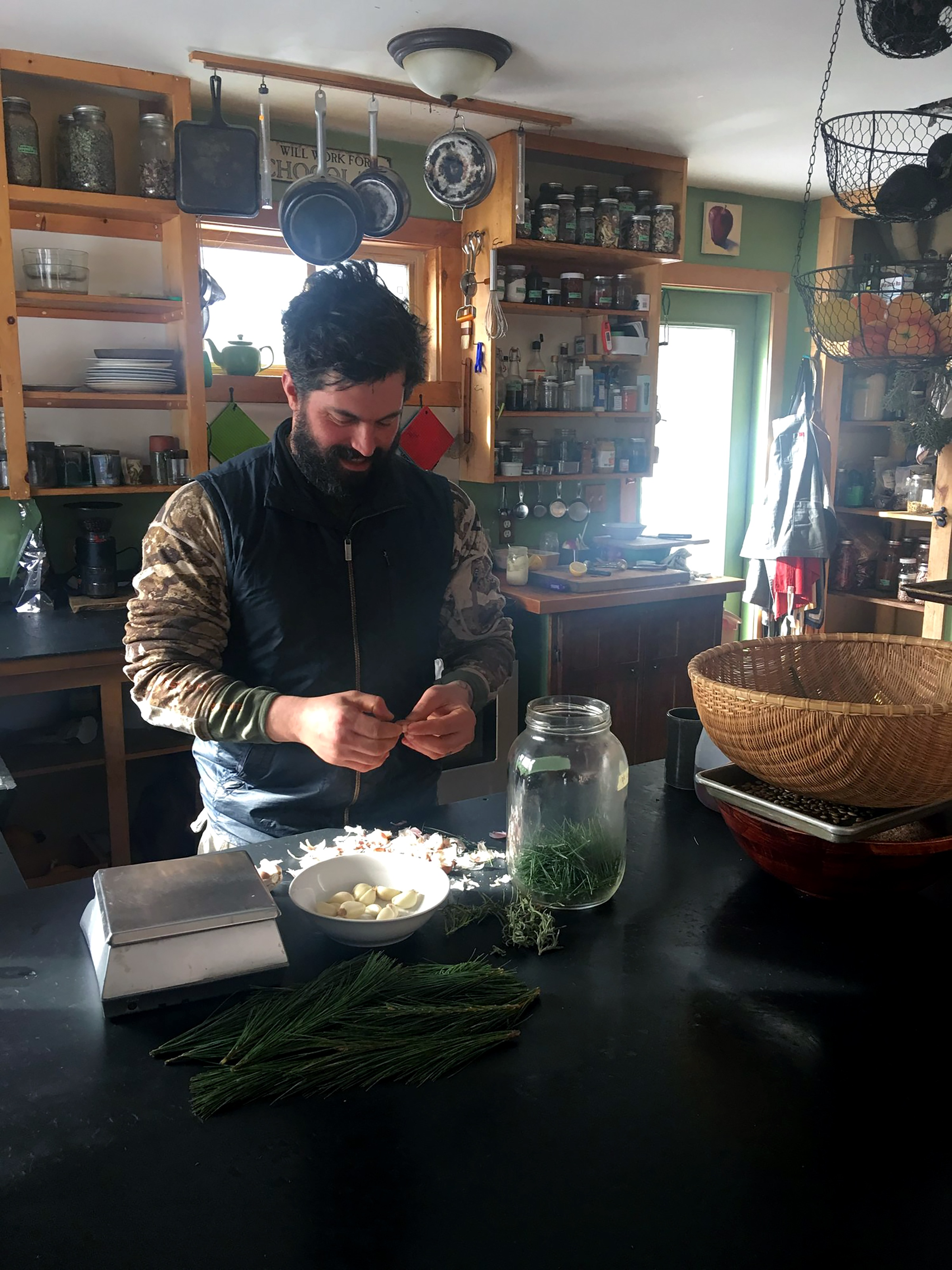 Bearded man in warm, rustic home kitchen making a preparation with fresh herbs