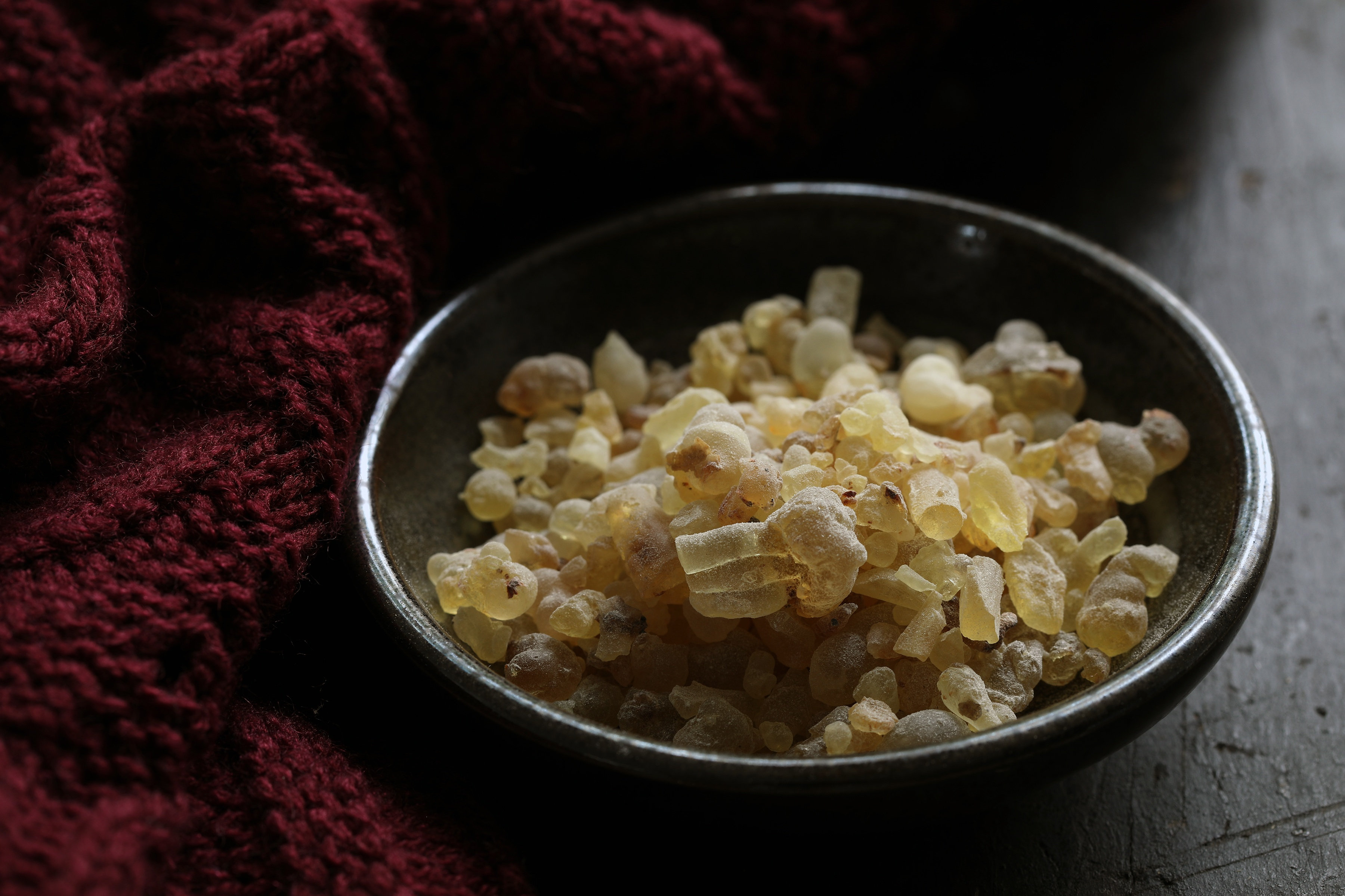 frankincense tears in a dark bowl next to a red knit scarf