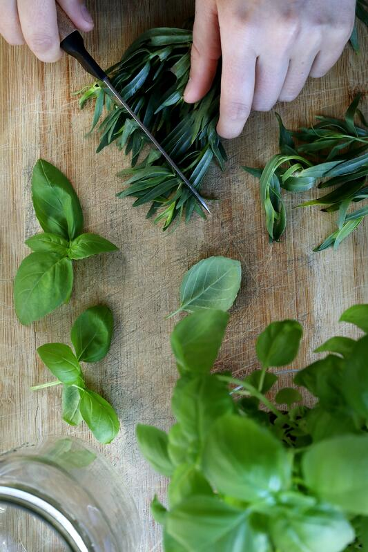 Hands chopping fresh vibrant herbs on wooden board