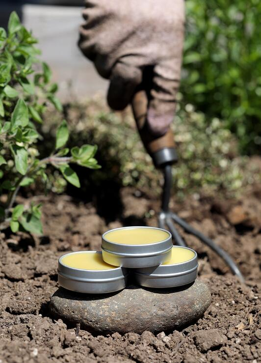 Herbal salve tins sitting on a rock in the garden next to gardening tools
