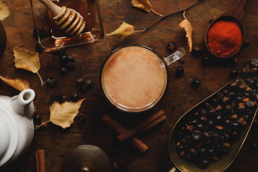 Gaurana seeds, mug with warm drink inside, tea pot, honey, cinnamon sticks on a table