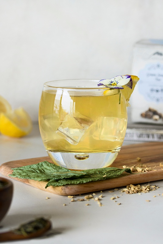 Clear glass of ginger palmer mocktail with ice cubes with lemon wedges and ginseng