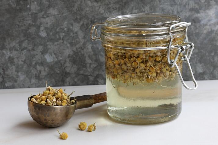 Pantry jar filled with vegetable glycerine and chamomile flowers to make an extraction