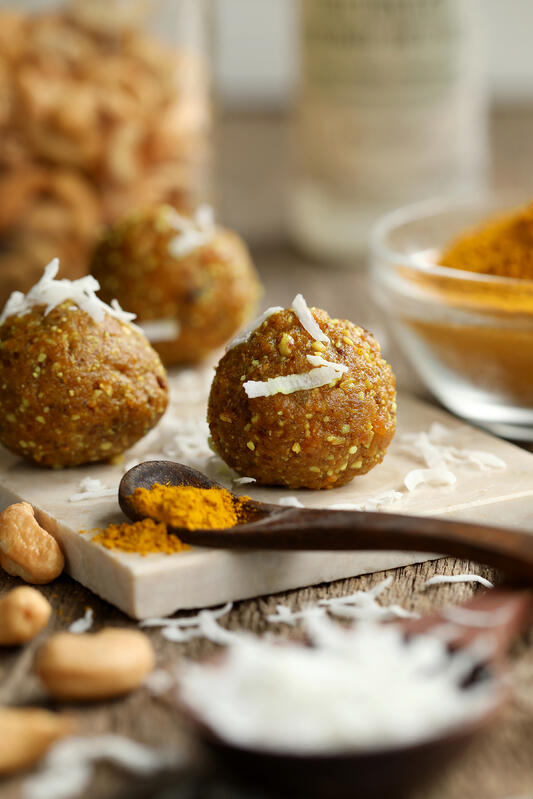 No bake date energy balls on board surrounded by ingredients and golden milk powder.