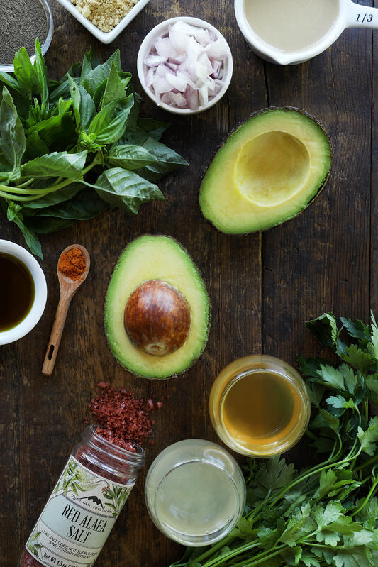 Fresh, colorful ingredients are arranged together including sliced avocado, minced shallots, basil, parsley, apple cider vinegar, red Alaea salt, and lemon juice, on a rustic wood table top.