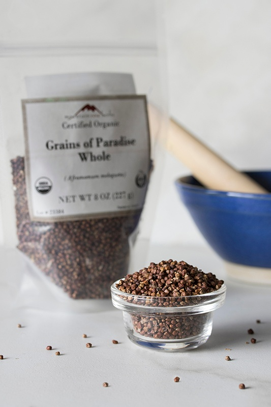 glass bowl filled with grains of paradise spice with bag of grains of paradise and mortar and pestle