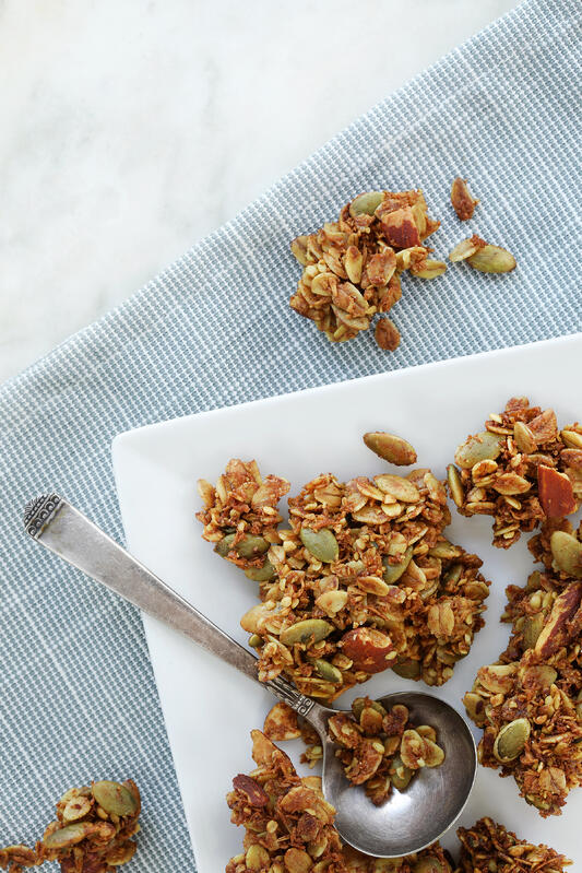 A plate of homemade granola with coconut, pumpkin seeds, almonds, and vanilla extract. Square plate on a blue serviette with freshly made granola.
