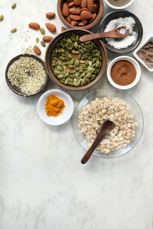 Ingredients are laid out to prepare a homemade granola featuring pepitas, almonds, whole oats, hemp seeds, and coconut flakes. Spices include turmeric, cardamom, cinnamon, and vanilla extract.