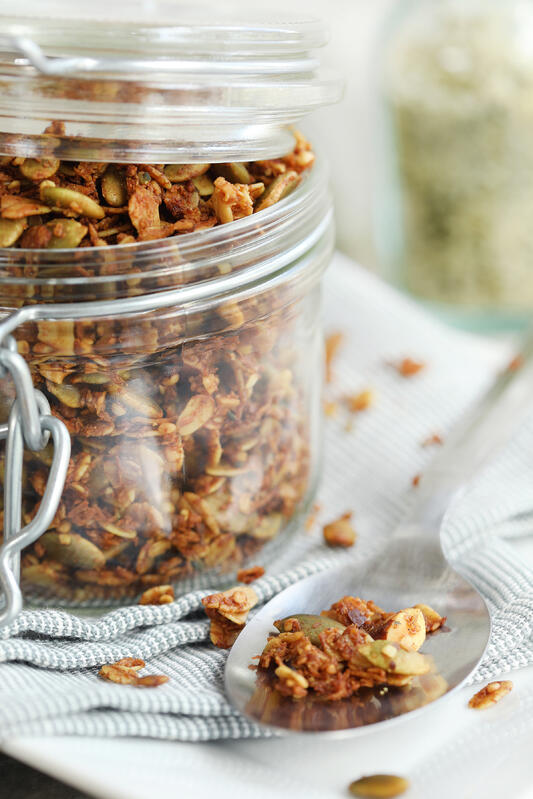 Pantry jar full of homemade granola featuring pumpkin seeds, hemp seeds, almonds, and coconut. Fresh and healthy homemade granola recipe for on the go snacking.