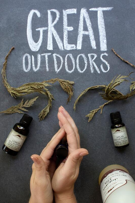 Hands rubbing oils together in glass bottle Great Outdoors essential oil fragrance recipe
