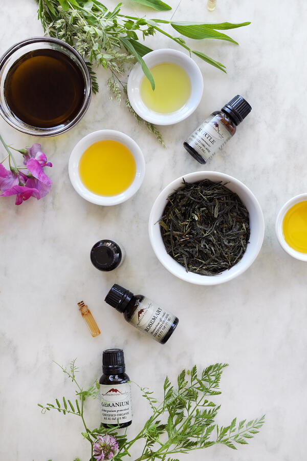 Ingredients are arranged in bowls for a green tea serum including a green tea herbal oil, various essential oils, and dried green tea leaves.
