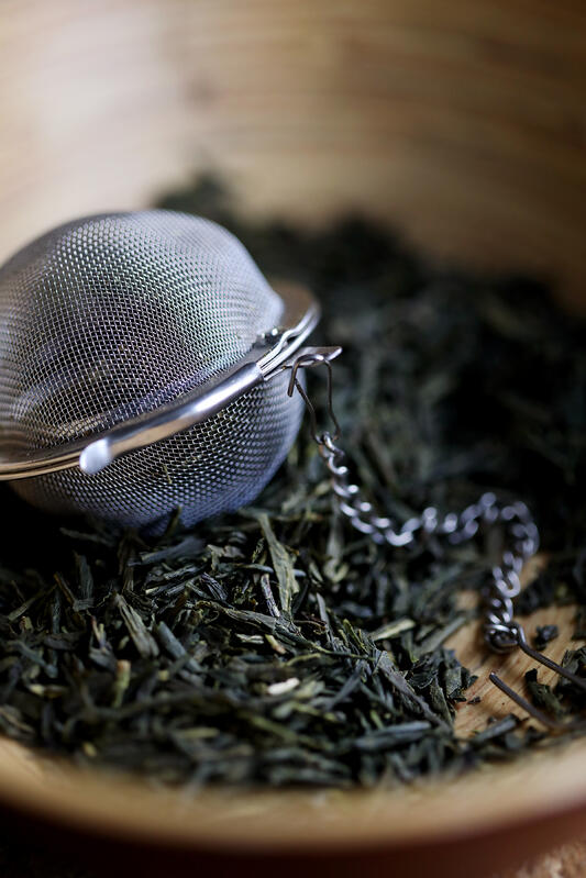 Dried green tea leaves with a mesh steel tea ball in a wooden bowl
