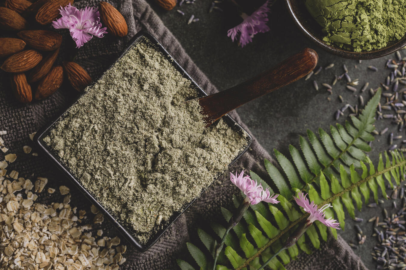 Matcha and lavender cleansing grains surrounded by almonds, oatmeal and lush ferns.