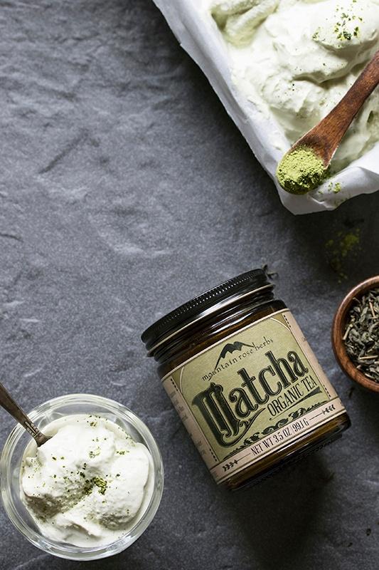 Bowl of matcha green tea ice cream with matcha powder and spoon