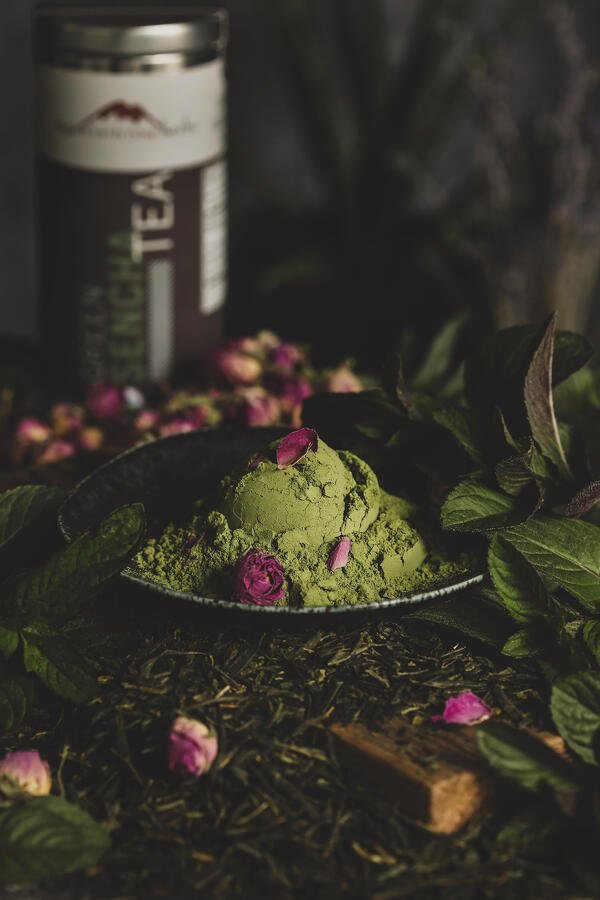 Vibrant matcha green tea in a bowl surrounded by beautiful rose petals.