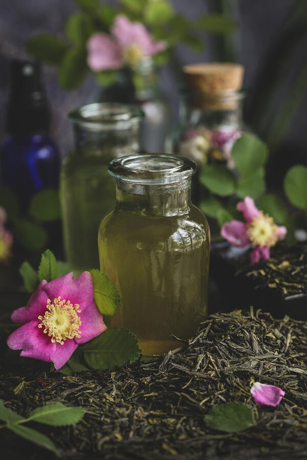 Green tea and rose toner in a glass jar surrounded by green sencha tea and flowers.