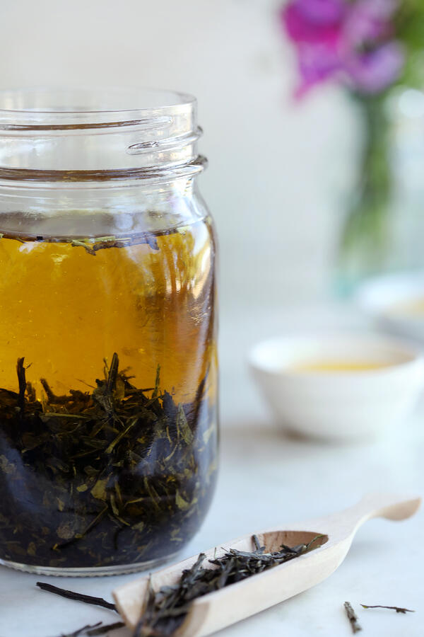 A mason jar filled with green tea leaves and organic olive oil left to steep. A wooden scoop in the foreground is filled with green tea leaves and bowls of oil in the background.