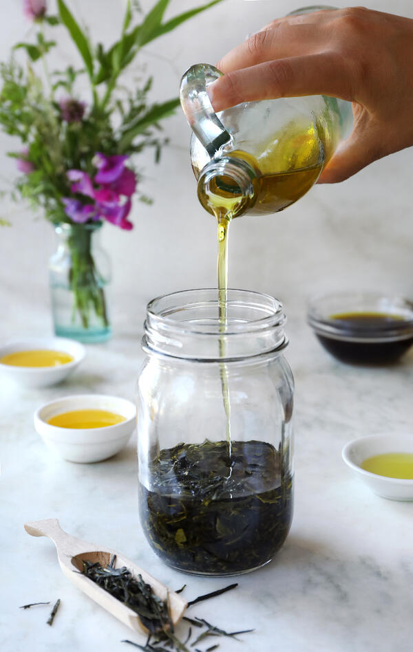 Organic olive oil being poured over dried green tea leaves in a clear mason jar. Bowls of different colored oils are arranged around with a wooden scoop of tea leaves on a white marble counter top.