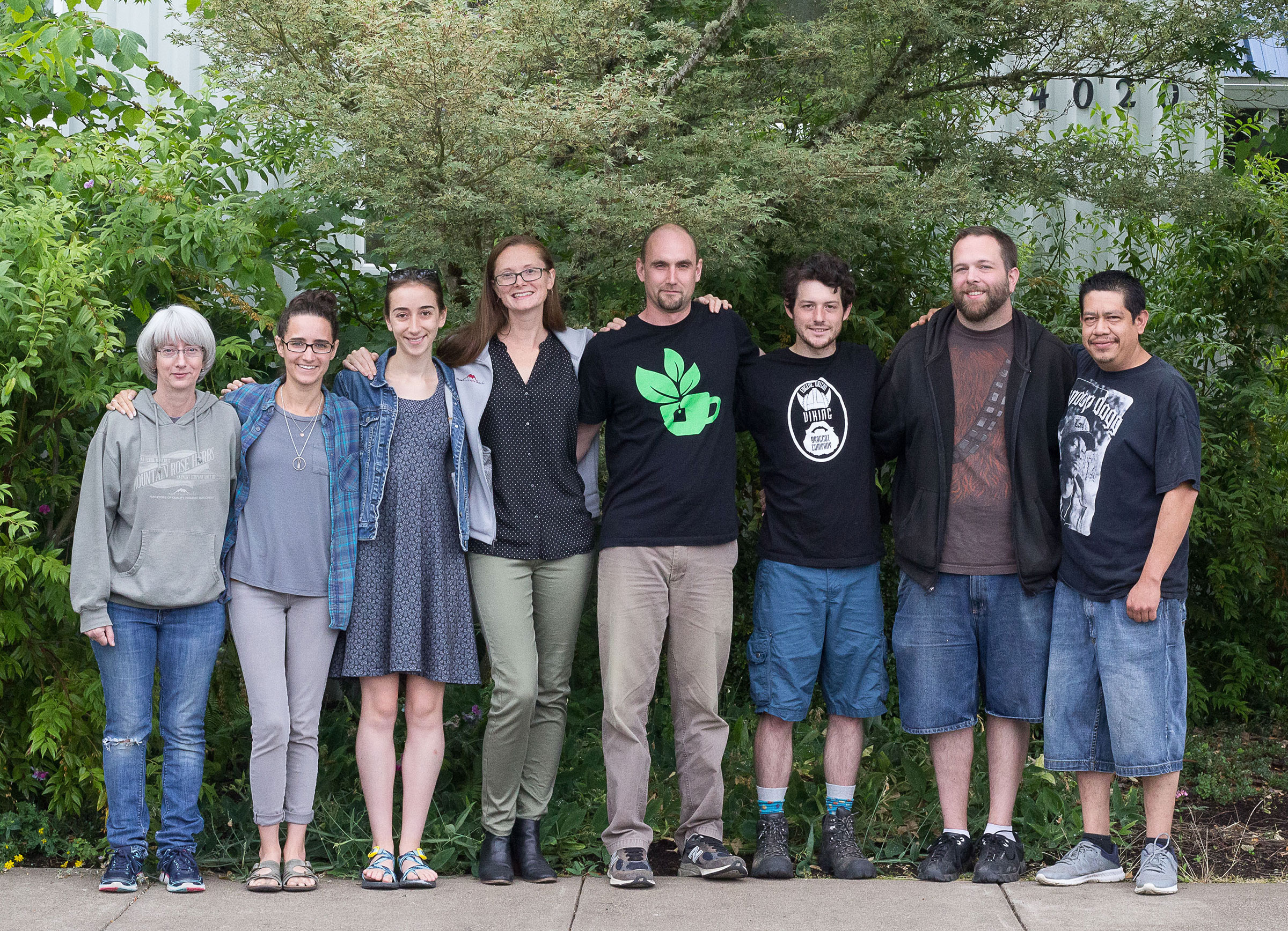Employees at Mountain Rose Herbs meet for a Green Team meeting, standing together outdoors