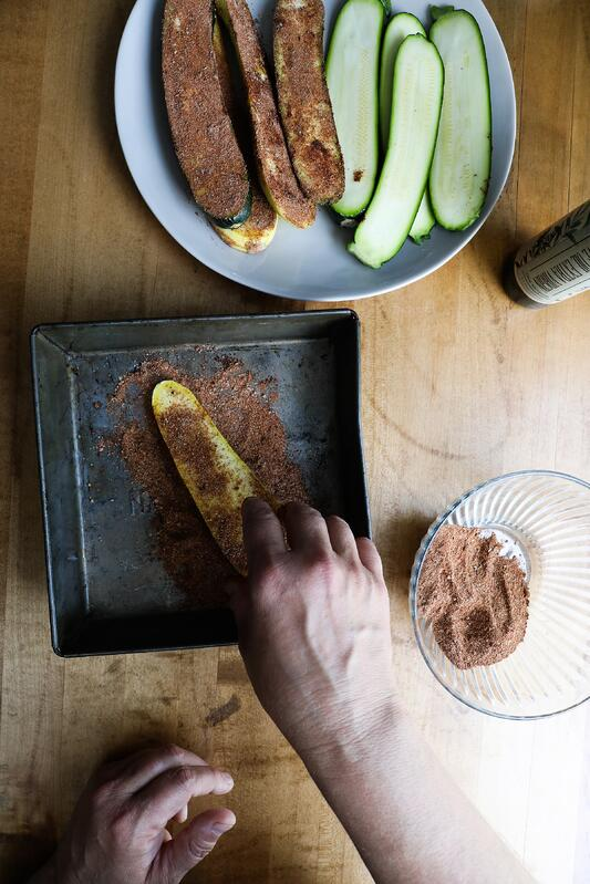 Hand placing squash slice onto a tray with adobo spice for marination and grilling