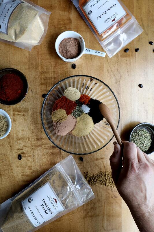 Hand using spoon to mix different spices in bowl to make adobo grilling rub for veggies