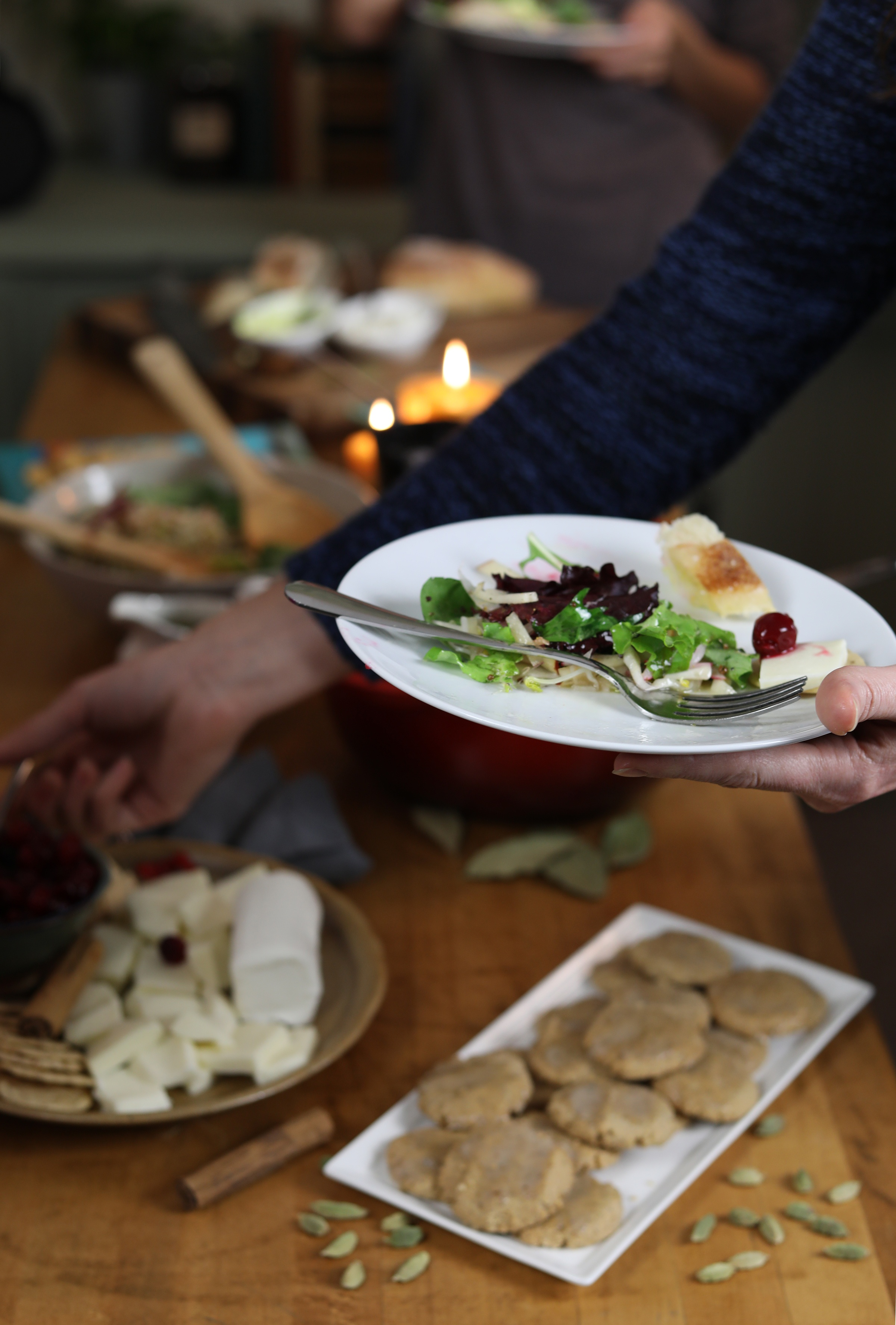 Hand holding fresh salad, reaching for cranberries  and cheese, hovering over group meal table