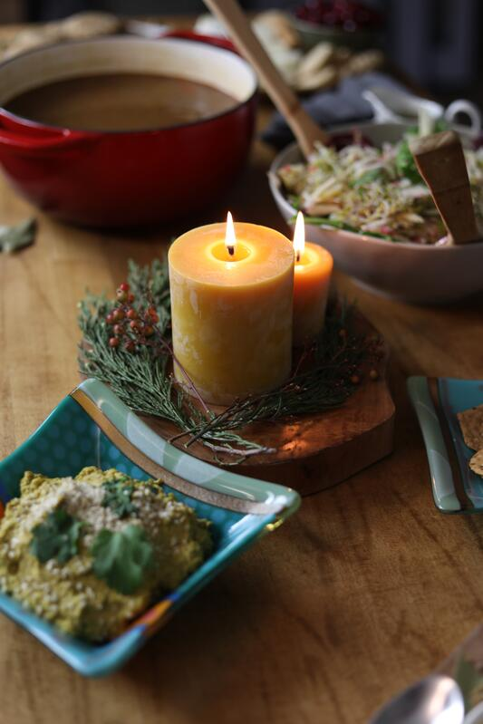 Beeswax candle in the middle of a table by fir wreath as decoration for group meal potluck during holiday