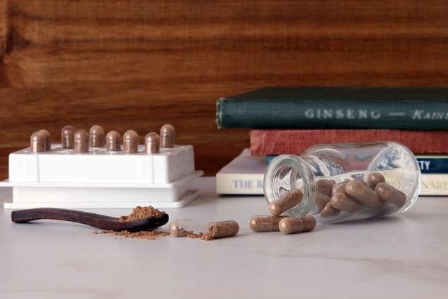 Jar of guarana capsules and guarana seed powder on counter next to capsule machine and books