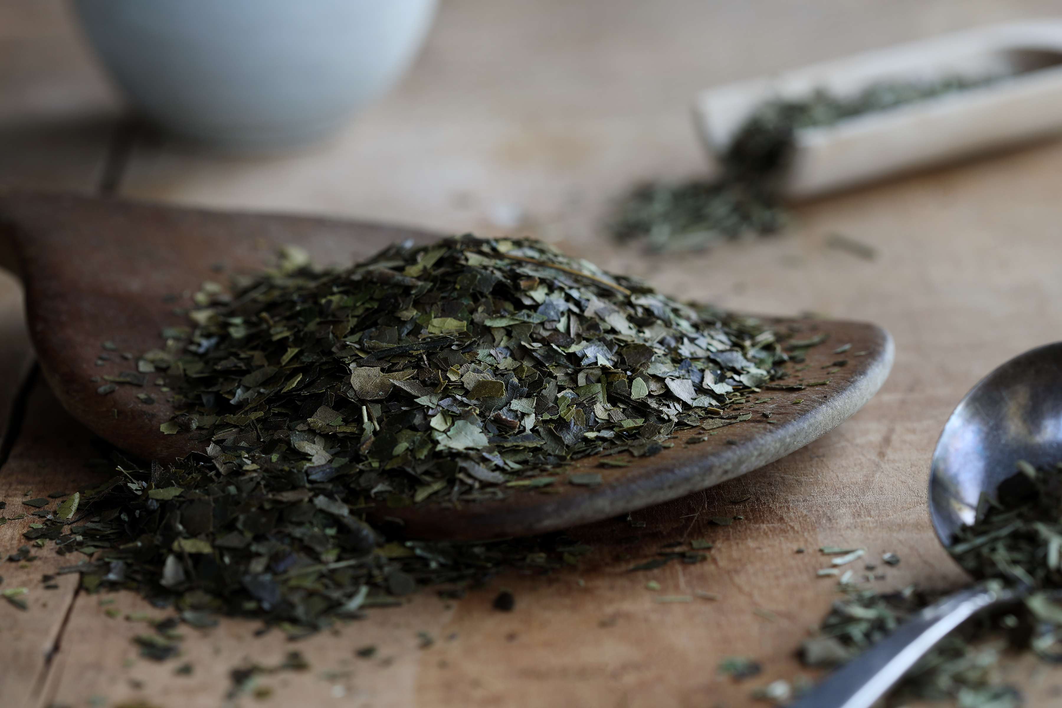 Spoon of green botanicals spilling onto rustic wooden table.