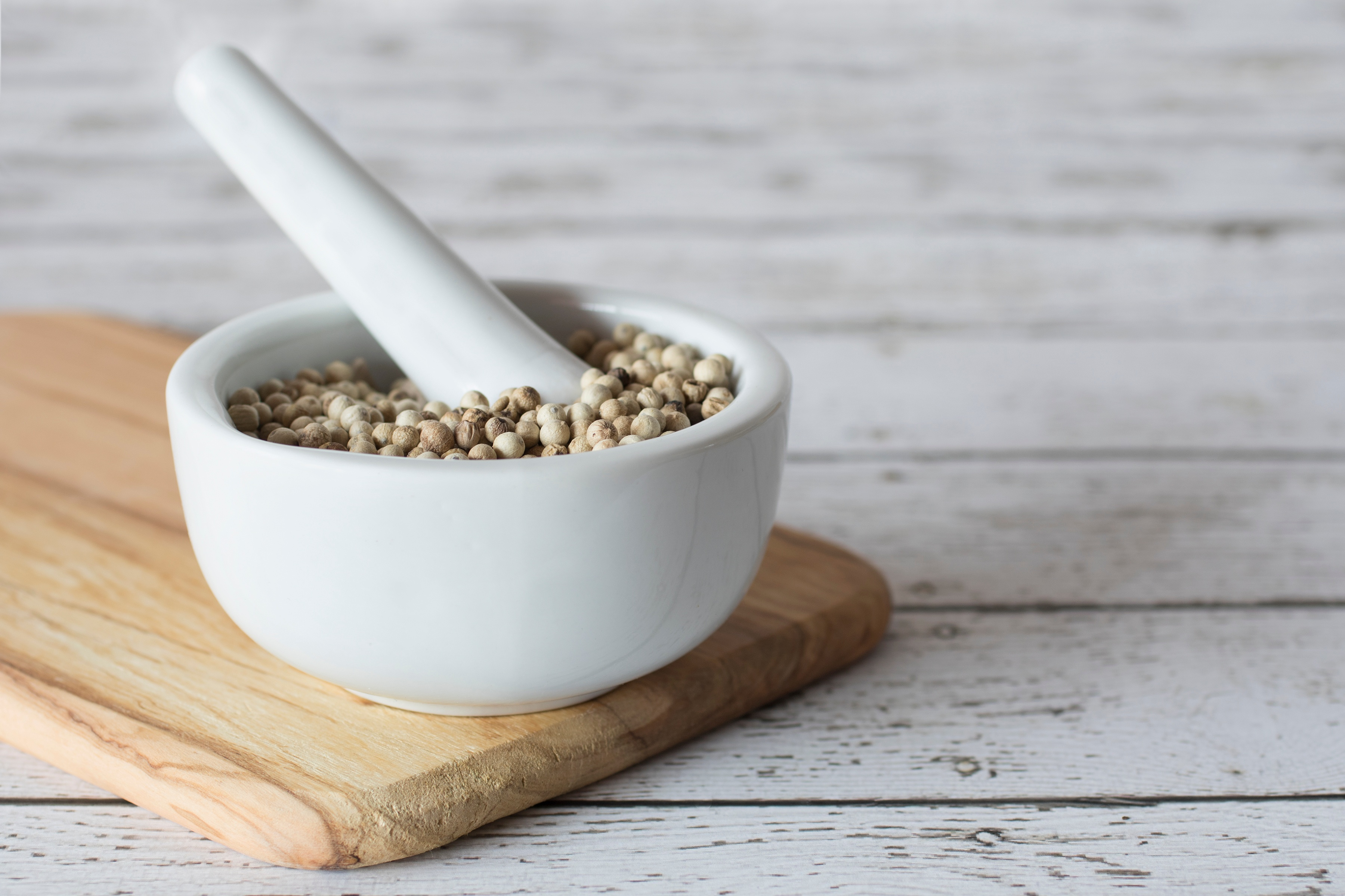 White peppercorns in a mortar on top of a chopping board with a pestle